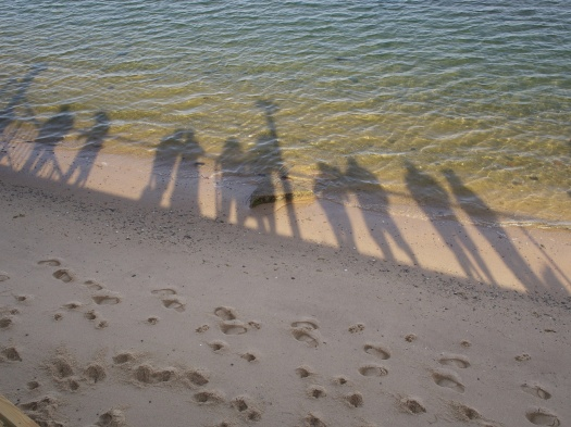 Looking over a deck in Provincetown, Cape Cod, I first noticed the many footprints in the sand and then the shadows of others looking out onto the ocean.