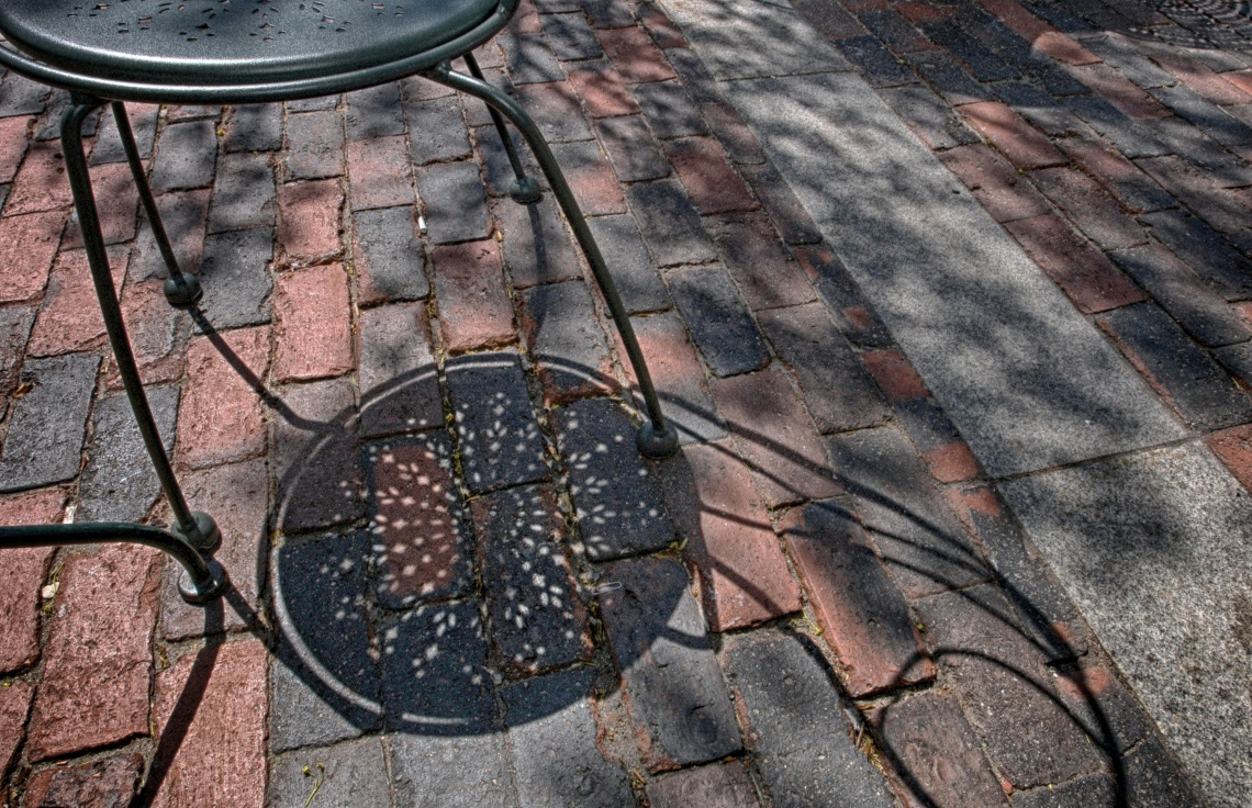 Shadows creeping along the pavement at an outdoor cafe.