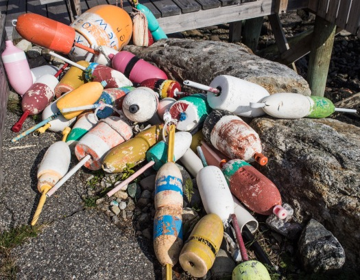Colorful lobster buoys thrown in an isolated corner on the pier in Boothbay, Maine.